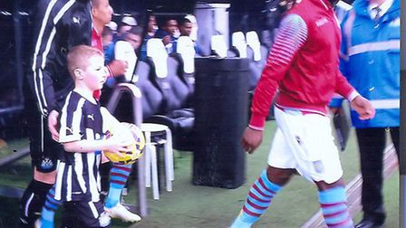 Marcus Neve walks out with Newcastle defender Mike Williamson.