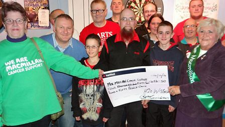 Members of the H2O darts team present the club's cheque to members of the Wisbech group of Macmillan