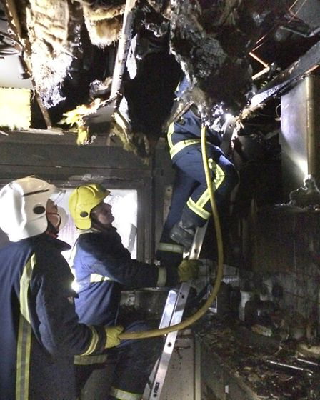 Firefighters survey the damage after the fire.