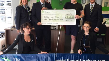 Building society manager David Boyce presents Billy Lee with the cheque, watched by colleagues.
