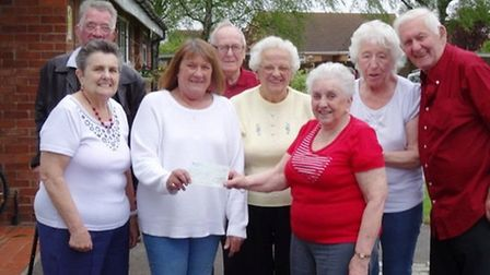 Mary Done, from the East Anglian Air Ambulance, receives a cheque from residents of Anchor Court, in