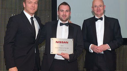 JS Holmes sales director Alex Holmes, centre, collects the Overall Retailer of The Year award from N