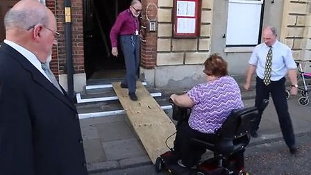 Cllr Alan Lay helps his wife Cllr Brenda Lay up the improvised ramp at Wisbech Town Hall.