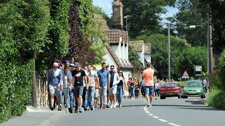 People walk to the scene of the fatal car crash in Worlington to lay flowers.