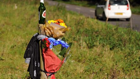 The floral tributes at the scene of the accident on the A1065 near the Desert Rats Memorial at Mundf