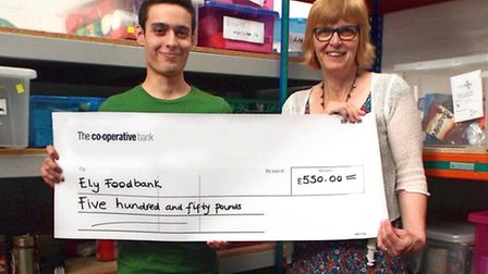 Will Law presents the cheque to Cathy Wright, project director of Ely Foodbank. Picture: SOPHIE WRIG