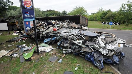 The overturned lorry at Five-Ways Roundabout at Barton Mills which has shed its load of scrap metal.
