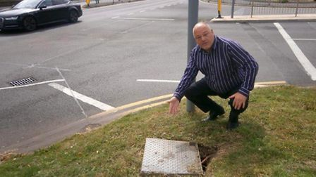 Cllr Paul Clapp next to the misplaced cover on the grass verge in Churchill Road, opposite Robert Ha