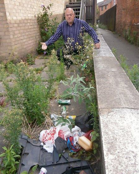Cllr Paul Clapp looks at some of the overgrown foliage and rubbish on the site of the building in Ch