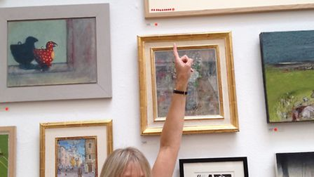 Louise Stebbing pointing to her work on display at The Royal Academy.