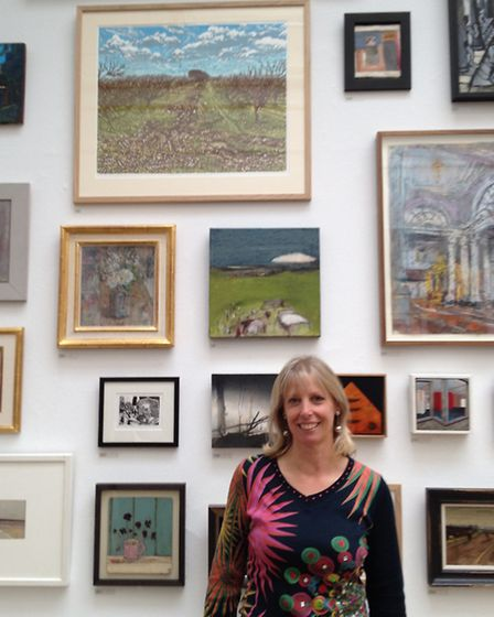 Louise Stebbing standing underneath her work at The Royal Academy.