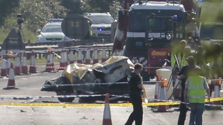 Emergency services attend the scene on the A27 after a plane crashed into cars on the major road dur