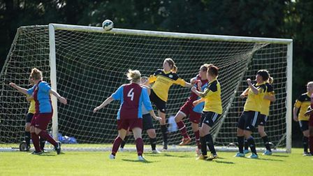 Hannah Johnson rises to head clear from a corner for March Town Ladies.
