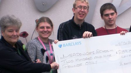 June Skinner presents a cheque for £209 to students from Meadowgate School