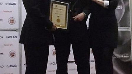 Burwell firefighter Simon Muir (centre) is presented with his individual achievement award at the 20