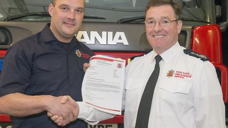 Chris Smalley receives an official Letter of Recognition from Essexs chief fire officer Adam Eckley.