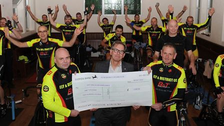 Ely and District Cycling Club members Steve Wells (left) and Derek Ricketts (right) hand over a cheq