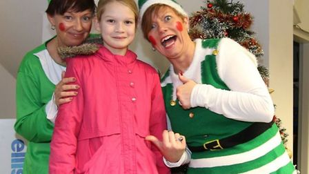 Ellis Winters & Co Christmas elves Tracy Raine (left) and Kim Puckering present Cleo Bailey from Gle