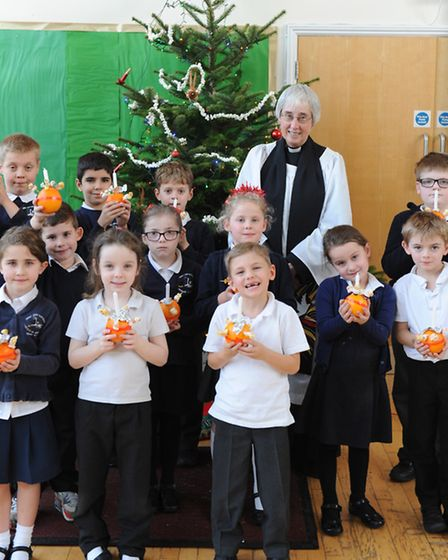 Pupils at Mepal and Witcham Christingle Service with Reverend Mary Hancock