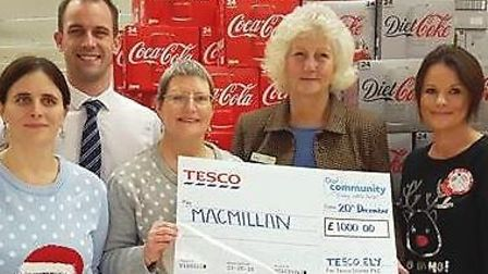 Angie Squires, holding the cheque, with Tesco Ely staff members