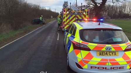 Police officers and a fire crew at the scene of the crash on New Road, Chatteris