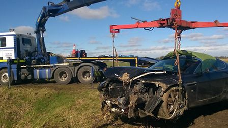 An Aston Martin Vantage is recovered after crashing on March Road.