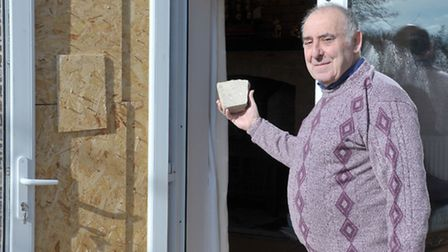 David Young with the concrete brick thieves used to smash through a door in Mr and Mrs Young's bunga