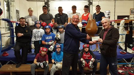 Trevor Stockbridge of March Lions hands over a cheque for £100 to March Boxing Club.