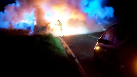 A vehicle is engulfed in flames after being involved in a three-car accident May 12, 2014, near RAF