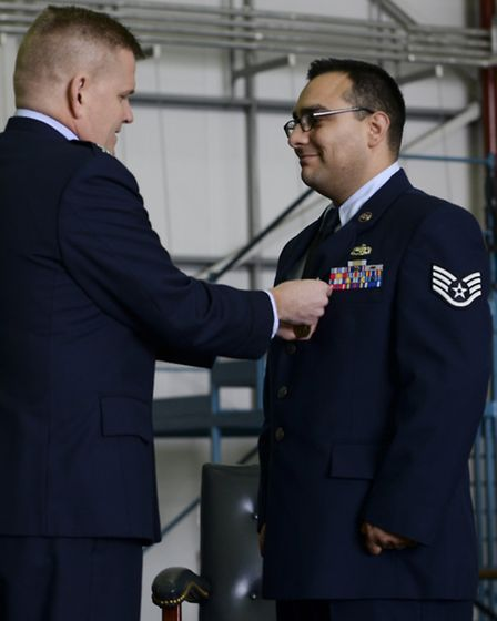 USAF Col Thomas Torkelson, 100th Air Refueling Wing commander, presents Staff Sgt Vicente Gomez, 100