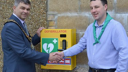 Mayor of March, Rob Skoulding, presents a defibrillator to March 1st Scouts leader, Gavin Philpott.