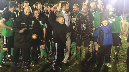 Littleport Town players and staff hold the Creake Charity Shield aloft.