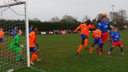 Alex Theobald rises to meet a corner for Ely City.
