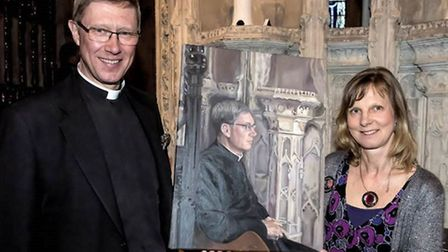 Mark Bonney, dean of Ely, pictured holding his portrait by local artist Caroline Forward