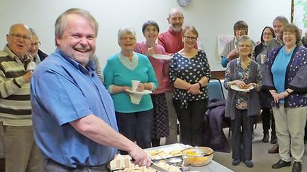 Archdeacon Hugh McCurdy cuts the cake at the Cherishing out Past, Building Our Future session.