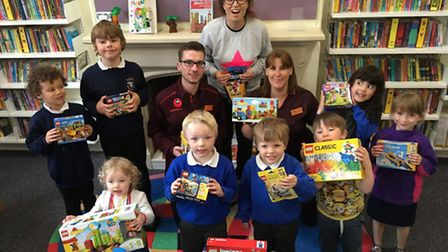 Caline Easey and Littleport Lego Club members receiving a donation of more Lego from Sainsbury's.