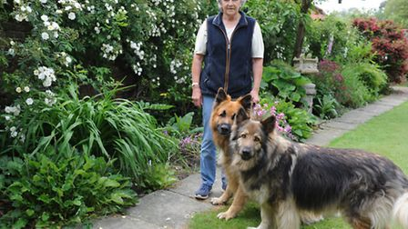 Diana Bullard, pictured her with her two dogs, is to open her nine-acre garden next month to raise m