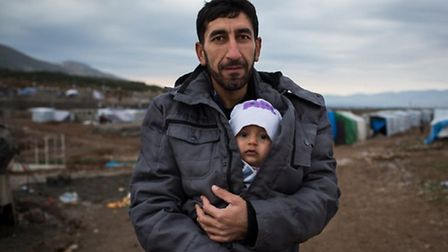 A Syrian refugee holds his young son in a refugee camp in northern Iraq. Refugees are to be rehomed