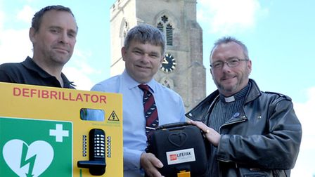 15th defib for March being put up at St Wendreda's Church Hall, March. Left: Electrician Darren Bigg