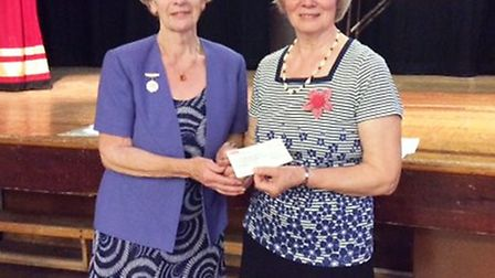 President of the City of Ely Flower Club, Joyce Svennson, presents a cheque for £250 to member of th