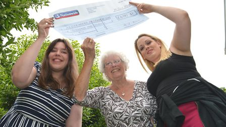 Skydiver (centre) Margaret Missin, presenting proceeds to Alzheimer's Reserach UK Fundraising Office