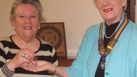 New president Mary Rone, right, giving past president's badge to Diana Goldstein