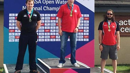 Ross Wisby, centre, after winning the 5,000m at the East Region Open Water championships.