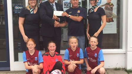 David Boyce, branch manager of The Nottingham hands a cheque for £100 over to March Rangers under 12