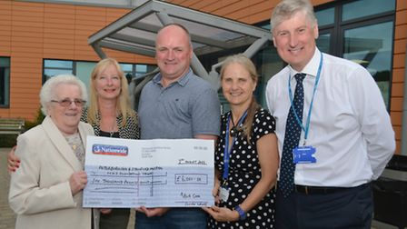 Mark Cross (centre) presents a cheque for £6,000 to the Oncology department at Peterborough City Hos