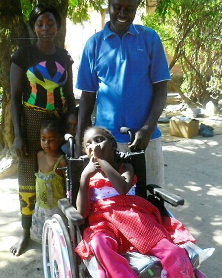 Rachel Mulongesha in her new wheelchair, surrounded by her friends and family, including her father