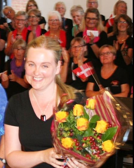 Kathryn Rowland, Sing! Choirs musical director, with flowers.