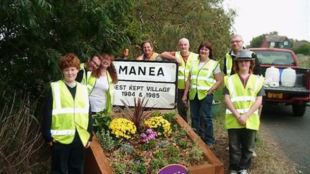 Manea Street Pride group helping keep the village tidy - alongside the sign that reminds them of wha