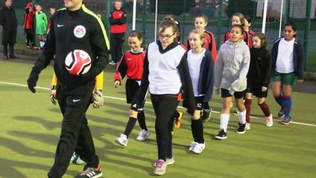 Craig Pawson leads out two of the girls' teams. Photo: RWT Photography