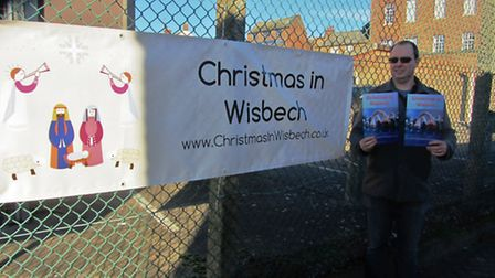 Wisbech Churches Together Chairperson, Matt McChlery standing next to the Christmas In Wisbech banne